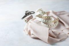 Todo para coser Tela beige, accesorios de costura y tijeras Fotos de archivo libres de regalías