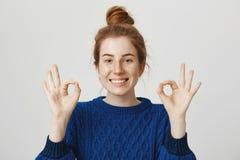Todo será autorización, le asegura Retrato de la mujer atractiva positiva del pelirrojo con el bollo que sonríe ampliamente mient Imagen de archivo
