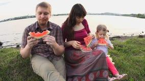 Todos juntos comen la familia feliz de la sandía en una comida campestre por la charca en un día de verano almacen de video