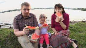 Todos juntos comen la familia feliz de la sandía en una comida campestre por la charca en un día de verano metrajes