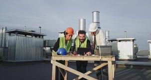 Todos os trabalhadores da construção são que cercam a tabuleta para ver a metragem final do que foi filmado na tabuleta video estoque