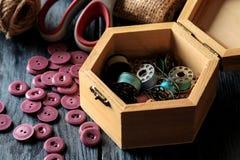 Toebehoren voor het naaien en handwerk kist met spoelenclose-up op een blauwe houten achtergrond royalty-vrije stock afbeeldingen