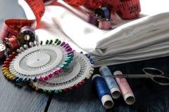 Toebehoren voor het naaien en handwerkdraad, stof, schaar, spoelen, spelden, centimeter op een blauwe houten achtergrond royalty-vrije stock afbeelding