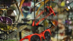 Toebehorenverkoop bij lokaal warenhuis, vrouwelijke klant die zonnebril kiezen stock footage