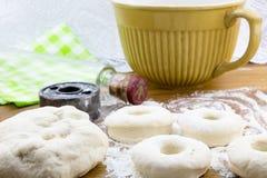 Toegenomen doughnutdeeg op gebloeide houten lijst met snijder en rolli stock foto's