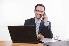 Toegewijde werknemer die met glazen bij telefoon glimlachen royalty-vrije stock fotografie