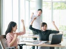 Toejuichend gelukkige bedrijfsmensen, hief het Gelukkige commerciële team met wapen zitting maandelijks bij bureau in bureau op t Stock Afbeeldingen