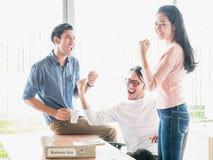 Toejuichend gelukkige bedrijfsmensen, hief het Gelukkige commerciële team met wapen zitting maandelijks bij bureau in bureau op t royalty-vrije stock afbeeldingen