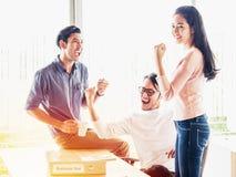 Toejuichend gelukkige bedrijfsmensen, hief het Gelukkige commerciële team met wapen zitting maandelijks bij bureau in bureau op t Royalty-vrije Stock Foto's