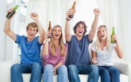 Toejuichende groep vrienden die de camera bekijken Royalty-vrije Stock Afbeelding