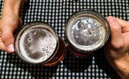 Toejuichingen: een paar overhandigt het vieren met bieren stock afbeeldingen