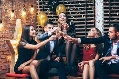 Toejuichingen! Groep vrienden die glazen champagne clinking tijdens pa stock afbeeldingen