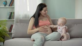 Toekomstige moeder die op geboorte van baby, leuk kind wat betreft zwangere buik wachten stock videobeelden