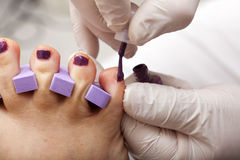 Toenails are painted in fuchsia color. At the end of a complete foot care treatment, the toenails are painted royalty free stock photos