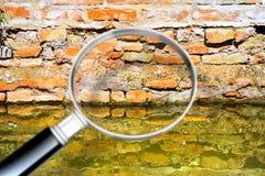 Toenemend die vocht op een bakstenen muur in een kanaalhoogtepunt van water - Conceptenbeeld door een vergrootglas wordt gezien royalty-vrije stock afbeelding