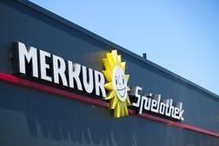 TOENISVORST, DUITSLAND - JUIN 28 2019: Sluit omhoog van tekst en zonembleem op zwarte voorgevel met blauwe hemel van Merkur Spiel royalty-vrije stock fotografie