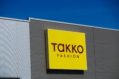 TOENISVORST, GERMANY - MARCH 22. 2019: Yellow logo of Takko fashionGerman fashion chain on a facade against clear blue sky royalty free stock photo