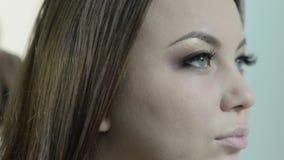 Toepassend make-up op een mooie jonge vrouw, die de wenkbrauwen invullen stock video