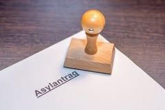 Toepassing voor asiel met houten zegel met het Duitse woord voor asielverzoek stock foto's