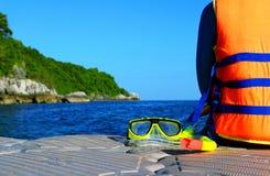 Toerisme die oranje reddingsvest of reddingsvest dragen en op de vlotter met geel het zitten snorkelt masker royalty-vrije stock foto