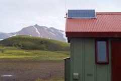 Toerisme in nationaal park Buitenfoto van weinig groen huis met zonnepaneel op rood dak en elektriciteit die van a lopen royalty-vrije stock foto's