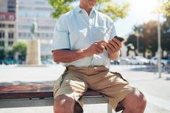 Toerist buiten rusten en het gebruiken van celtelefoon Stock Foto's
