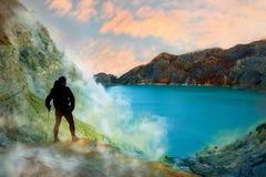Toerist in de krater van een vulkaan Zwavelrotsen, vulkanisch blauw zuurrijk meer en roze zonsopgang Een gevaarlijke reis in de k stock foto