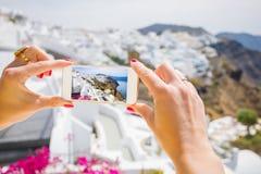 Toerist die beeld van Santorini met mobiele telefoon nemen stock foto