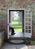 Toerist die bij de tuin van het landlandgoed rust Stock Foto