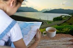 Toerist die de kaart op haar handen binnen bekijken bij de Ratchaprapha-dam Stock Afbeeldingen