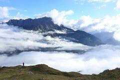 Toerist die de prachtige mening van alpiene die bergen bewonderen door overzees van wolken ~ worden omringd Stock Foto