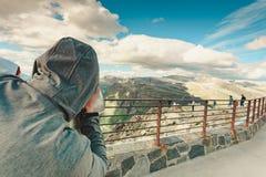 Toerist die door verrekijkers in bergen, Noorwegen kijken royalty-vrije stock fotografie