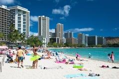 Toerist die en op het strand Waikiki in Hawaï zonnebaden surfen. Royalty-vrije Stock Foto