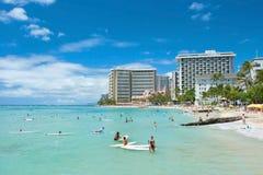 Toerist die en op het Waikiki-strand in Hawaï zonnebaden surfen. Stock Fotografie