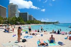 Toerist die en op Waikiki-strand op Hawaï Oahu zonnebaden surfen Stock Foto