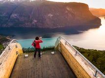Toerist die fjord van mening over Stegastein-gezichtspunt Noorwegen genieten stock afbeelding