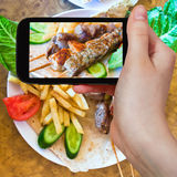 Toerist die foto van de Arabische kebabs van de vleespennenmengeling nemen stock foto