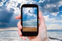 Toerist die foto van zonnestralen over Dode Overzees nemen Stock Fotografie