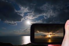 Toerist die foto van zonsondergang op Dode Overzees nemen Stock Foto's