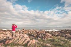 Toerist die met binoculair op de rotsachtige kustlijn in DE Kelders, Zuid-Afrika bekijken, beroemd voor walvis het letten op Wint stock afbeeldingen