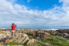 Toerist die met binoculair op de rotsachtige kustlijn in DE Kelders, Zuid-Afrika bekijken, beroemd voor walvis het letten op Wint stock foto's