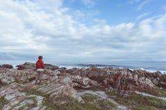 Toerist die met binoculair op de rotsachtige kustlijn in DE Kelders, Zuid-Afrika bekijken, beroemd voor walvis het letten op Wint stock foto
