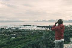 Toerist die met binoculair op de rotsachtige kustlijn in DE Kelders, Zuid-Afrika bekijken, beroemd voor walvis het letten op Wint royalty-vrije stock foto