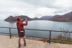 Toerist die met slimme telefoon het landschap fotograferen in Cape Town, op de Atlantische kustlijn van Zuid-Afrika stock afbeelding