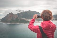 Toerist die met slimme telefoon het landschap fotograferen in Cape Town, op de Atlantische kustlijn van Zuid-Afrika stock foto