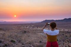 Toerist die met smartphone de overweldigende mening van onvruchtbare vallei in de Namib-woestijn, majestueuze bezoekeraantrekkeli stock afbeeldingen