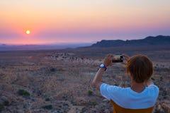 Toerist die met smartphone de overweldigende mening van onvruchtbare vallei in de Namib-woestijn, majestueuze bezoekeraantrekkeli royalty-vrije stock foto