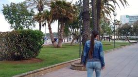 Toerist die op de straat met palmen lopen stock videobeelden