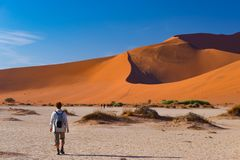 Toerist die op de toneelduinen van Sossusvlei, Namib-woestijn, het Nationale Park van Namib Naukluft, Namibië lopen Avontuur en e stock foto