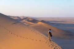 Toerist die op de toneelduinen van Sossusvlei, Namib-woestijn, het Nationale Park van Namib Naukluft, Namibië lopen Middaglicht a royalty-vrije stock foto